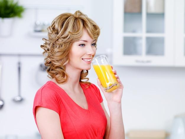 Linda mulher sorridente bebendo suco de laranja fresco