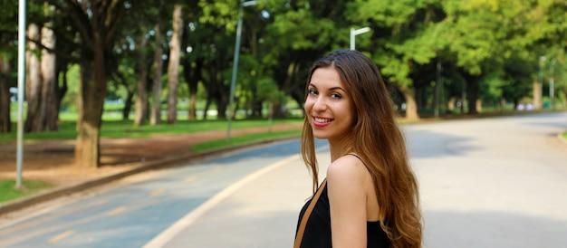 Linda mulher sorridente caminhando no parque do ibirapuera, em são paulo. vista panorâmica do banner.