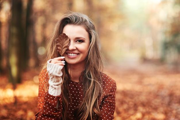 Linda mulher sorridente cobrindo os olhos com folhas outonais