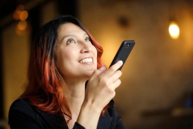 Linda mulher sorridente com cabelo ruivo usa o celular.
