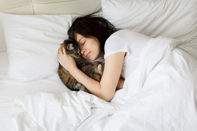 Linda mulher sorridente com os olhos fechados, deitada na cama e abraçando o gato