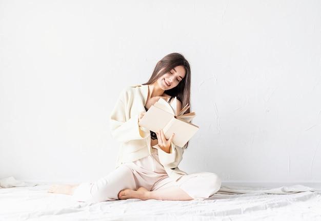 Linda mulher sorridente com roupas confortáveis em casa lendo um livro sentada no chão sorrindo