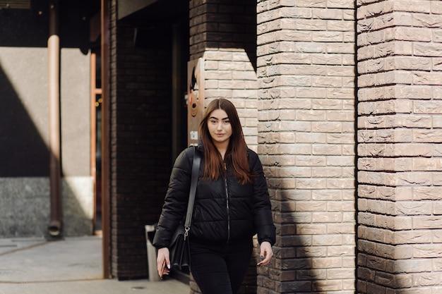 Linda mulher sorridente com smartphone caminhando na rua