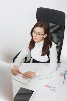 Linda mulher sorridente de cabelos castanhos de terno e óculos, sentada na mesa, trabalhando no computador com um monitor contemporâneo com documentos em um escritório leve, as mãos no teclado