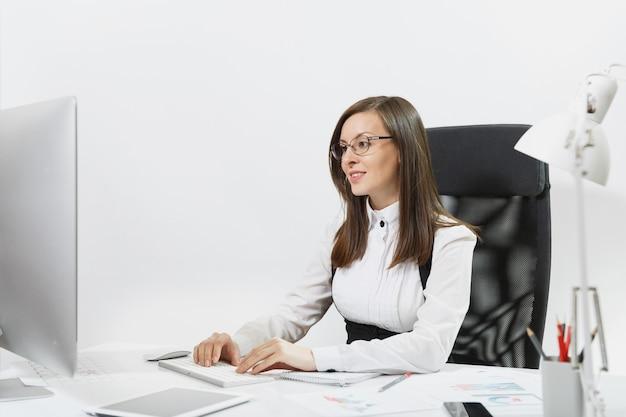 Linda mulher sorridente de cabelos castanhos de terno e óculos, sentada na mesa, trabalhando no computador com um monitor moderno com documentos em um escritório leve, as mãos no teclado,