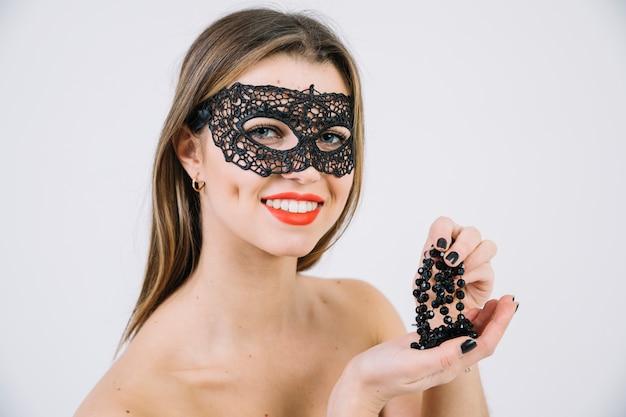 Linda mulher sorridente em preto carnaval máscara segurando colar de miçangas pretas