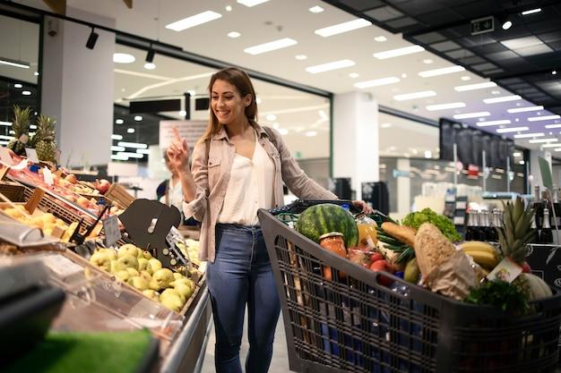 Linda mulher sorridente escolhendo que fruta comprar no supermercado