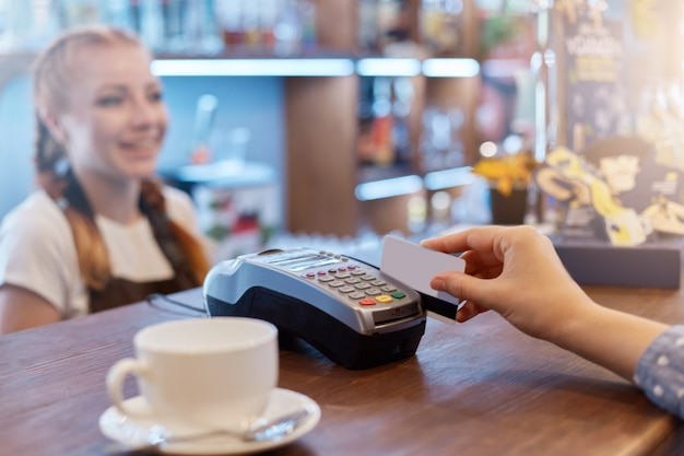 Linda mulher sorridente fala com o cliente que paga pelo terminal para o sistema de cartão de crédito