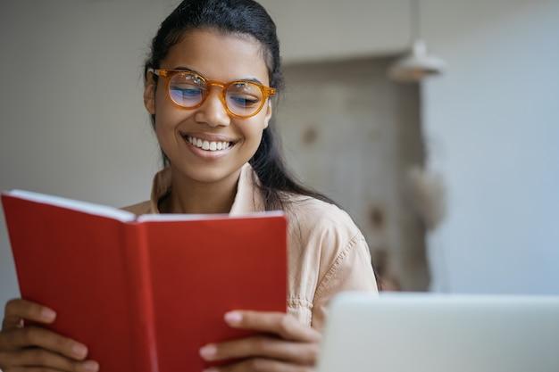 Linda mulher sorridente lendo livro, trabalhando, sentada na biblioteca moderna