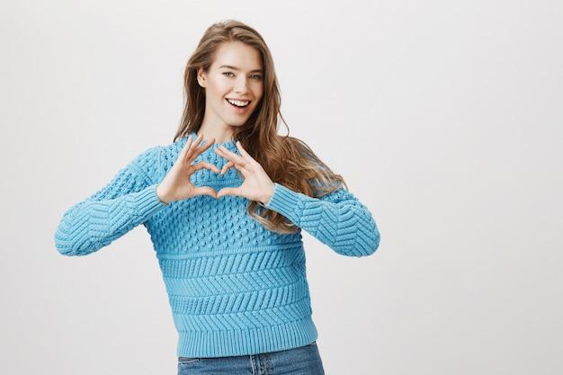 Linda mulher sorridente romântica mostra sinal de coração