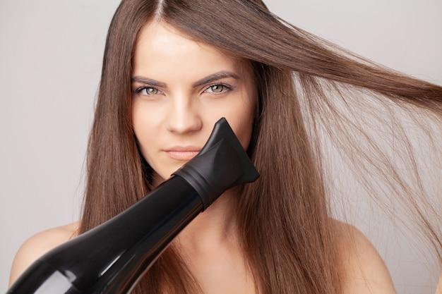 Linda mulher sorridente secando seus longos cabelos com secador