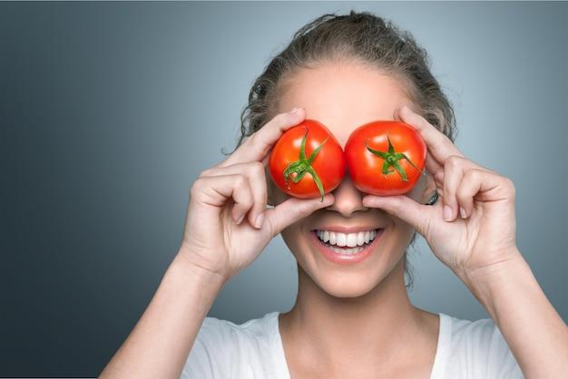 Linda mulher sorridente segurando dois tomates maduros diante de seus olhos.