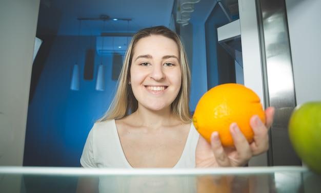 Linda mulher sorridente segurando uma laranja e olhando dentro da geladeira