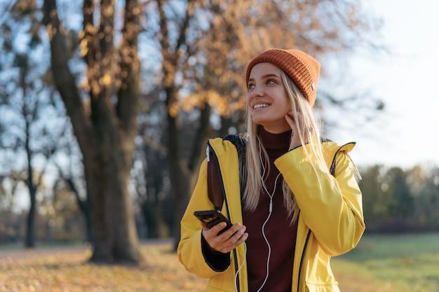 Linda mulher sorridente usando um chapéu de capa de chuva e ouvindo música em uma viagem de inspiração de outono no parque