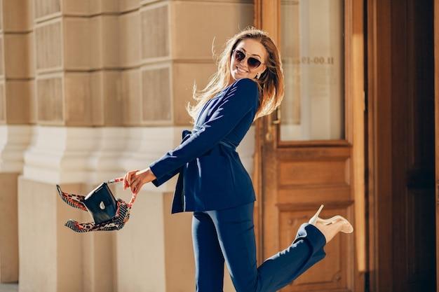 Linda mulher sorridente, vestida com um terno elegante e óculos de sol, caminhando pela rua, sorrindo no tempo ensolarado.
