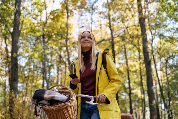 Linda mulher sorridente, vestindo uma capa de chuva amarela, andando de bicicleta na floresta. conceito de viagens.