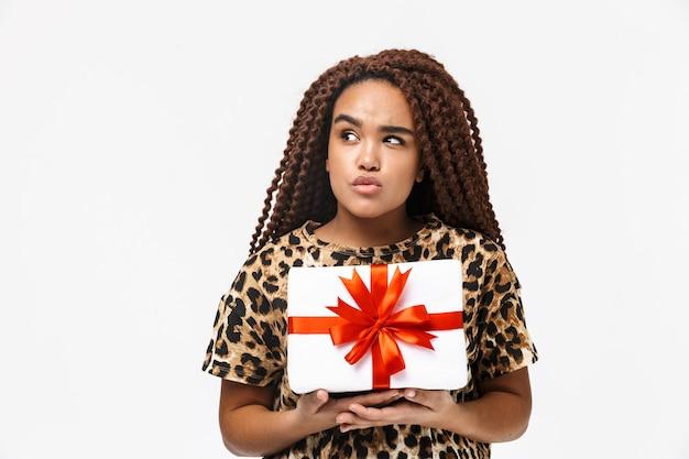 Linda mulher sorrindo e segurando uma caixa de presente com um laço em pé, isolado contra uma parede branca