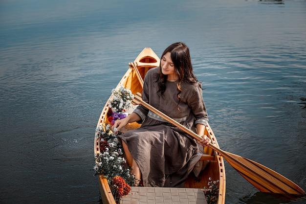 Linda mulher sozinha em um barco de madeira flutuando no lago - privacidade com a natureza