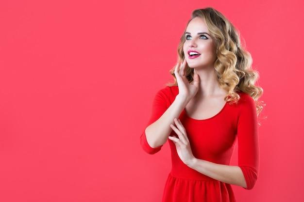 Linda mulher surpresa com cabelo brilhante em um vestido vermelho. isolado.