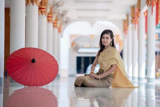Linda mulher tailandesa em traje tradicional no templo da tailândia