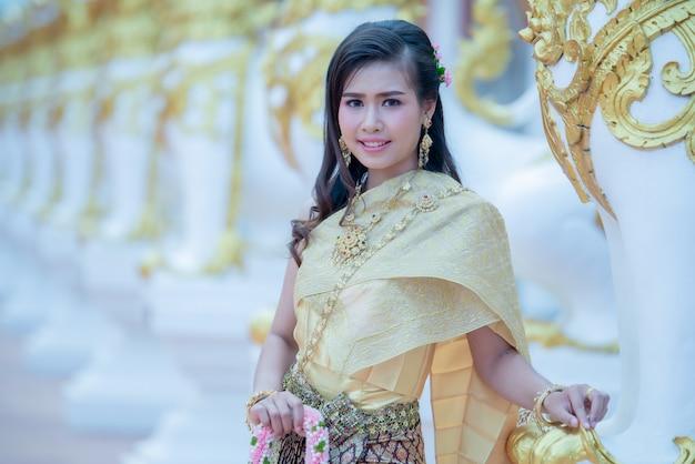 Linda mulher tailandesa em traje tradicional no templo de phra that choeng chum tailândia