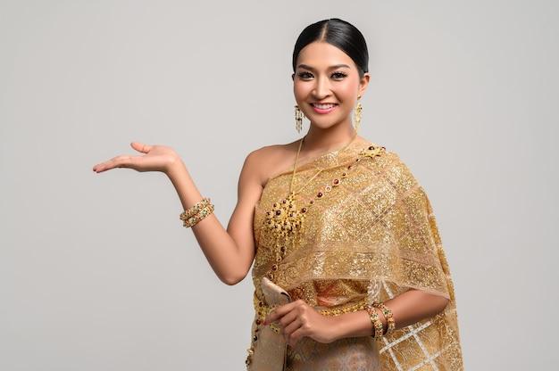 Linda mulher tailandesa usa roupas tailandesas e abre a mão para a direita