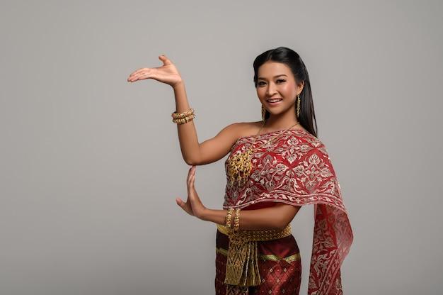 Linda mulher tailandesa usando vestido tailandês e dança tailandesa