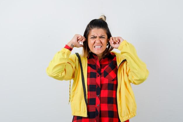 Linda mulher tapando as orelhas com os dedos na camisa, jaqueta e parecendo irritada, vista frontal.