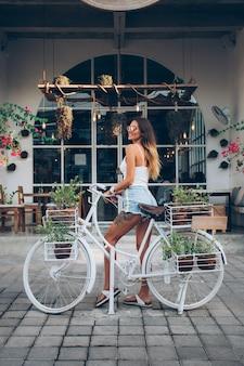 Linda mulher tatuada caucasiana em shorts jeans e top branco fica de bicicleta no fundo do café de rua.