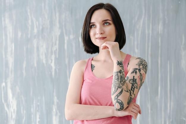 Linda mulher tatuada perto da parede do grunge