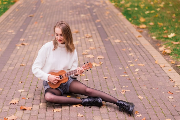 Linda mulher tocando guitarra cavaquinho ao ar livre em uma floresta de outono