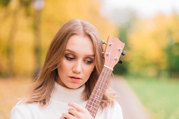 Linda mulher tocando guitarra cavaquinho ao ar livre na floresta de outono