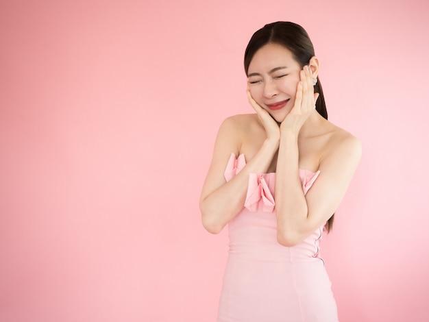 Linda mulher tocando sua bochecha com os dedos, menina asiática é muito feliz, moda doce