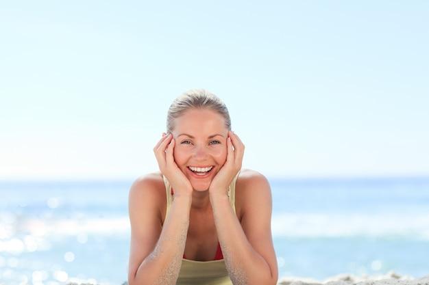 Linda mulher tomando banho de sol na praia