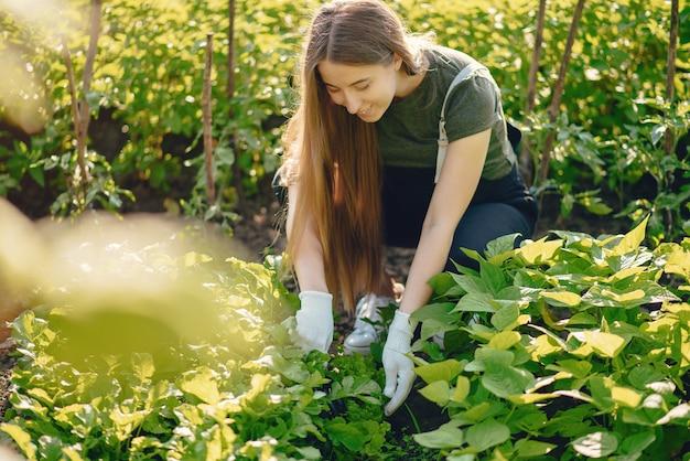 Linda mulher trabalha em um jardim perto da casa