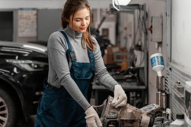 Linda mulher trabalhando em uma oficina de automóveis