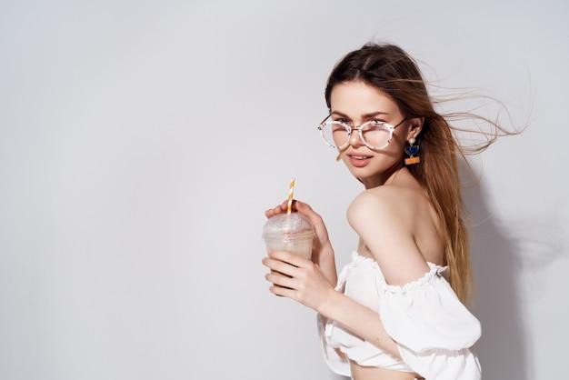 Linda mulher um copo com uma bebida na mão moda luz de fundo. foto de alta qualidade
