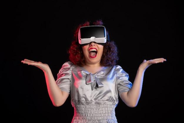 Linda mulher usando fone de ouvido de realidade virtual no visual de tecnologia de visão de jogo escuro