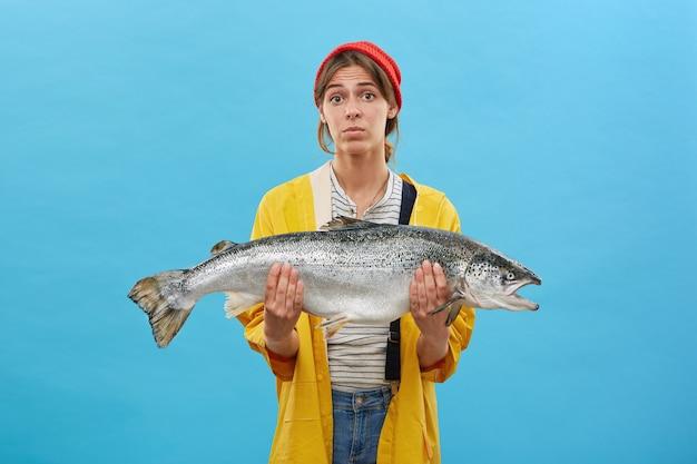Linda mulher usando um chapéu vermelho, capa de chuva amarela e segurando um peixe enorme nas mãos