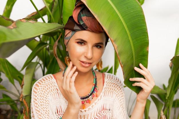 Linda mulher usando um lenço colorido como um turbante e brincos grandes e redondos