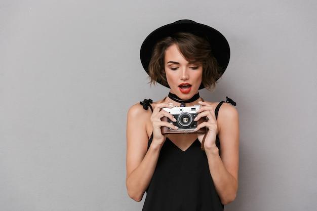 Linda mulher usando vestido preto e chapéu fotografando na câmera retro, isolada sobre uma parede cinza