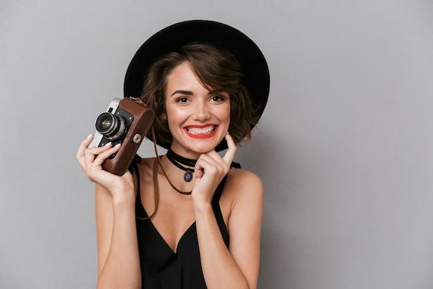 Linda mulher usando vestido preto e chapéu segurando uma câmera retro, isolada sobre uma parede cinza