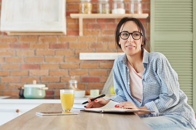 Linda mulher vestida casualmente, usa óculos, senta-se na mesa da cozinha de madeira,
