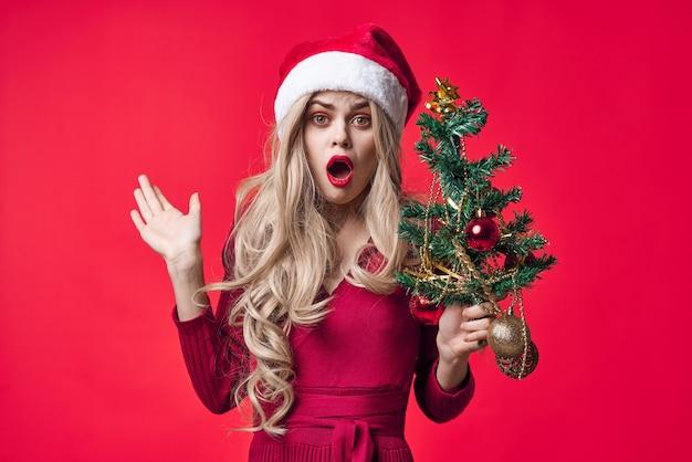Linda mulher vestida de papai noel árvore de natal brinquedos fundo rosa