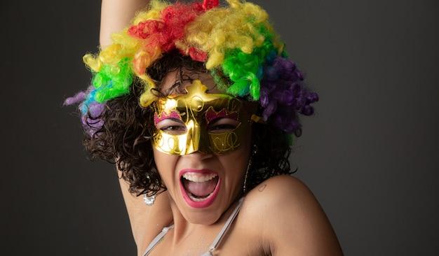 Linda mulher vestida para a noite de carnaval. mulher sorridente pronta para curtir o carnaval com uma peruca e máscara coloridas