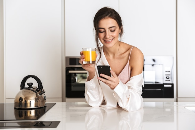 Linda mulher vestindo roupas de seda, bebendo suco na cozinha e usando o celular preto com um sorriso
