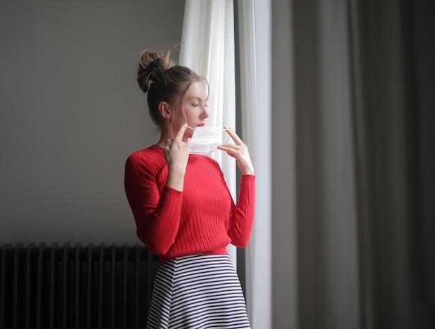 Linda mulher vestindo uma camisa vermelha e uma máscara cirúrgica perto de uma janela - pandemia