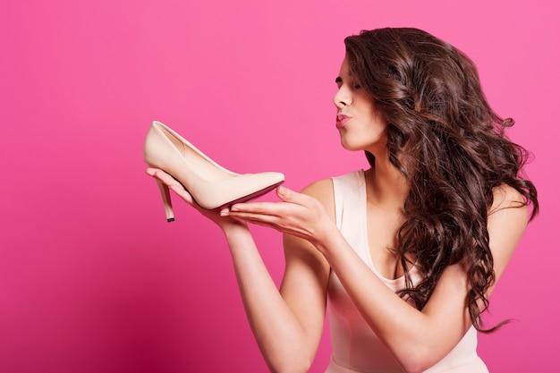 Linda mulher viciada em compras beijando salto alto