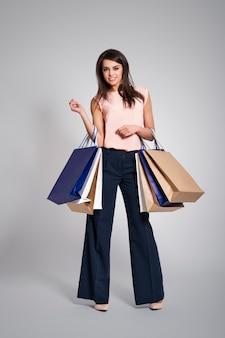 Linda mulher viciada em compras com sacolas de compras