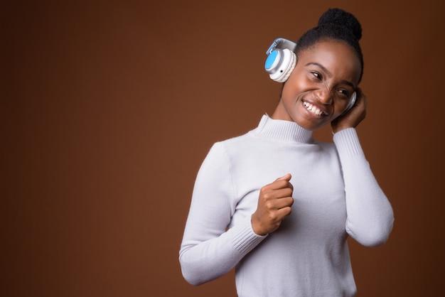 Linda mulher zulu africana ouvindo música usando fones de ouvido